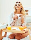 Blonde Frau der jungen Schönheit, die in frühem sonnigem MOR des Betts frühstückt Stockfoto