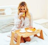 Blonde Frau der jungen Schönheit, die in frühem sonnigem MOR des Betts frühstückt Lizenzfreie Stockfotos