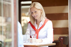 Blonde Frau an der Kaffeestube Stockfotografie