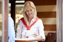 Blonde Frau an der Kaffeestube Stockfoto