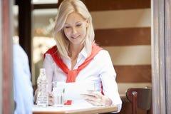 Blonde Frau an der Kaffeestube Stockbild
