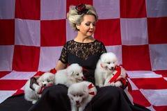 Blonde Frau in der Krone mit flaumigen Welpen Stockfoto