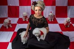 Blonde Frau in der Krone mit weißen Welpen Stockfoto