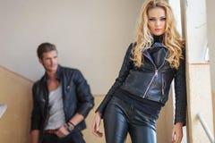 Blonde Frau in der ledernen Kleidung steht vor ihrem Liebhaber Stockfoto