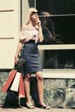 Blonde Frau der Mode in der Sonnenbrille mit Einkaufstaschen Stockfoto