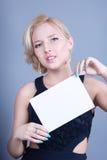 Blonde Frau der Mode, die leere Anschlagtafel hält Stockfoto