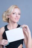 Blonde Frau der Mode, die leere Anschlagtafel hält Lizenzfreie Stockbilder
