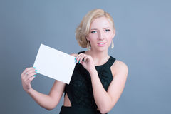 Blonde Frau der Mode, die leere Anschlagtafel hält Stockfotos