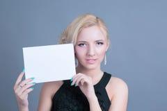 Blonde Frau der Mode, die leere Anschlagtafel hält Lizenzfreie Stockfotos