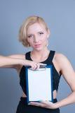 Blonde Frau der Mode, die leere Anschlagtafel hält Stockbilder