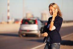 Blonde Frau der Mode, die um das Telefon im Freien ersucht Stockfotos