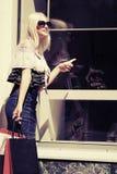 Blonde Frau der Mode mit Fenster der Einkaufstaschen im Einkaufszentrum Stockfotos