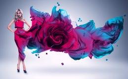 Blonde Frau in der Rosa- und Blaurose kleiden an Stockfoto