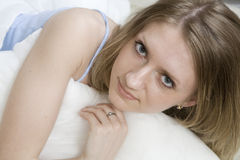 Blonde Frau der Rotation, die auf Bett liegt Stockfotos