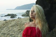 Blonde Frau der Schönheit auf dem Strand nahe dem Felsen Lizenzfreie Stockfotografie