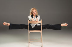 Blonde Frau der Schönheit auf Stuhl in der Balletthaltung Lizenzfreie Stockbilder