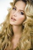 Blonde Frau der Schönheit mit langem Abschluss des gelockten Haares oben Stockfoto