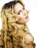 Blonde Frau der Schönheit mit langem Abschluss des gelockten Haares oben lokalisiert, Haare Lizenzfreie Stockfotos