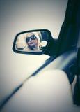 Blonde Frau in der Sonnenbrille, die im Autorückspiegel schaut Stockbild