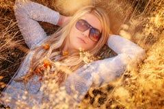 Blonde Frau in der Sonnenbrille, die im goldenen Gras liegt Stockfotos