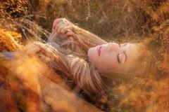 Blonde Frau in der Sonnenbrille, die im goldenen Gras liegt Lizenzfreie Stockfotos