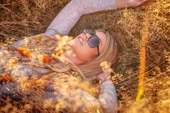 Blonde Frau in der Sonnenbrille, die im goldenen Gras liegt Stockfotografie