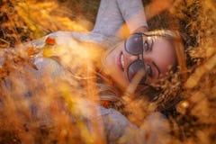 Blonde Frau in der Sonnenbrille, die im goldenen Gras liegt Lizenzfreie Stockfotografie