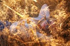 Blonde Frau in der Sonnenbrille, die im goldenen Gras liegt Stockbild
