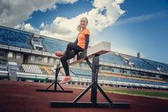 Blonde Frau in der Sportkleidung, die Übungen tut Stockfotografie