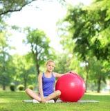 Blonde Frau in der Sportkleidung, die auf einem Gras mit pilates Ball sitzt Stockbild