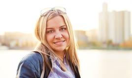 Blonde Frau in der Stadt bis zum sonnigem Tag Stockfotos