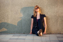Blonde Frau der traurigen jungen Mode, die an der Wand sitzt Stockfoto