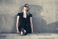 Blonde Frau der traurigen jungen Mode in der Sonnenbrille, die an der Wand sitzt Lizenzfreies Stockbild