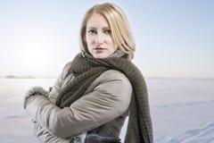 Blonde Frau in der warmen Kleidung über Winterhintergrund Lizenzfreie Stockfotos