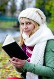 Blonde Frau in der weißen Schutzkappe und im Schal mit Buch Stockbilder