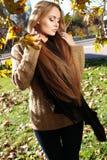 Blonde Frau in der zufälligen gemütlichen Kleidung, werfend im Herbstpark auf Lizenzfreie Stockfotos