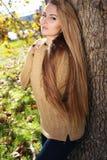Blonde Frau in der zufälligen gemütlichen Kleidung, werfend im Herbstpark auf Stockbild