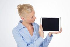 Blonde Frau des Geschäfts, die den Tablettenschirm betrachtet Stockfoto