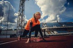 Blonde Frau des Läufers im Schwarzen mit orange Sportkleidung Lizenzfreies Stockbild