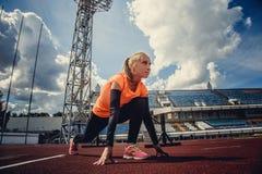 Blonde Frau des Läufers im Schwarzen mit orange Sportkleidung Stockfotos
