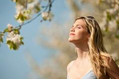 Blonde Frau des langen Haares unter blühendem Baum Lizenzfreie Stockfotografie