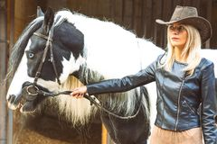 Blonde Frau des schönen Landhausstils mit Schwarzweiss-Pferd Lizenzfreies Stockfoto