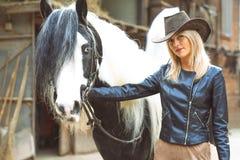 Blonde Frau des schönen Landhausstils mit Schwarzweiss-Pferd Stockfotografie