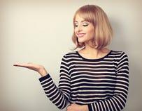 Blonde Frau des schönen Makes-up, die herein auf etwas hält und schaut Stockbilder