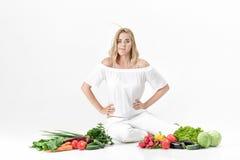 Blonde Frau des schönen Umkippens in der weißen Kleidung und in den vielen Frischgemüse auf weißem Hintergrund Diät Stockfotografie