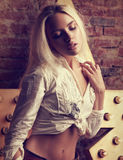 Blonde Frau des sexy Makes-up, die im weißen shi aufwirft und sich berührt Stockfoto