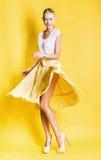 Blonde Frau des sexy Tanzens im gelben Rock Stockfotografie