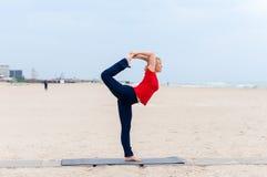 Blonde Frau des sportlichen Sitzes in der roten und dunkelblauen Sportkleidung draußen ausarbeitend am Sommertag, Natarajasana tu Stockbilder
