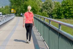 Blonde Frau, die über einer Fußgängerbrücke rüttelt Stockfotografie
