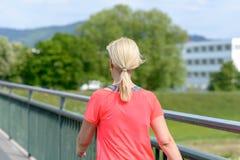 Blonde Frau, die über einer Fußgängerbrücke schreitet Lizenzfreies Stockbild